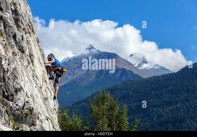Slim male rock climber in blue on steep rock face, with blue sky mountains and clouds - Stock Image