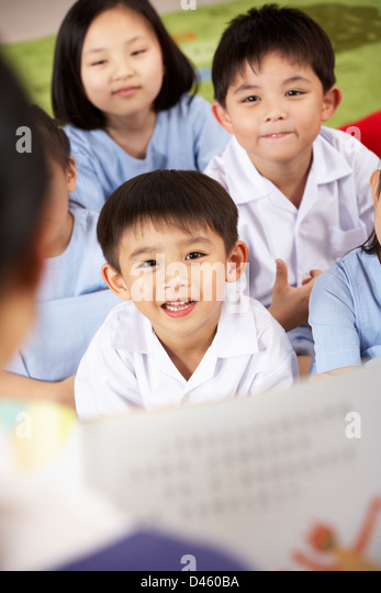 Teacher Reading To Students In Chinese School Classroom - Stock Image