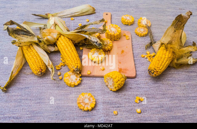 Sliced corn on the cob on chopping board, with whole corn on cob - Stock Image