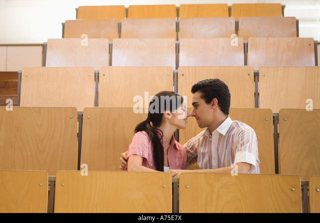 Students kissing in empty classroom - Stock Image