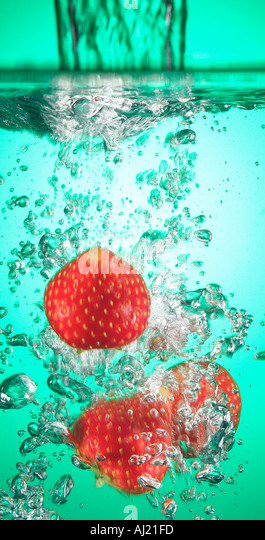 strawberries falling into coloured water - Stock Image