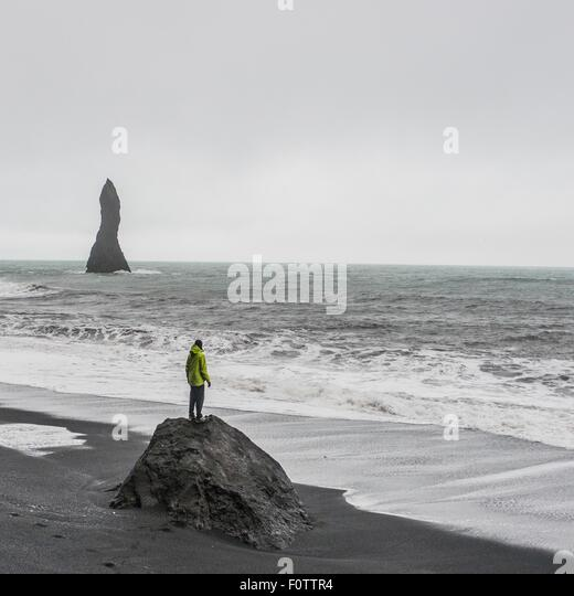 Young male tourist looking out to sea from rock formation,  Reynisfjara, Iceland - Stock Image