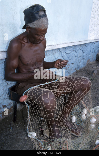 West Indies St. Lucia Vieux Fort senior Black male fisherman repairs net - Stock Image