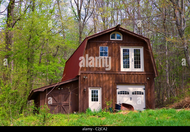 A large wooden barn with red metal roof designed to be use as a residence (if needed). - Stock Image