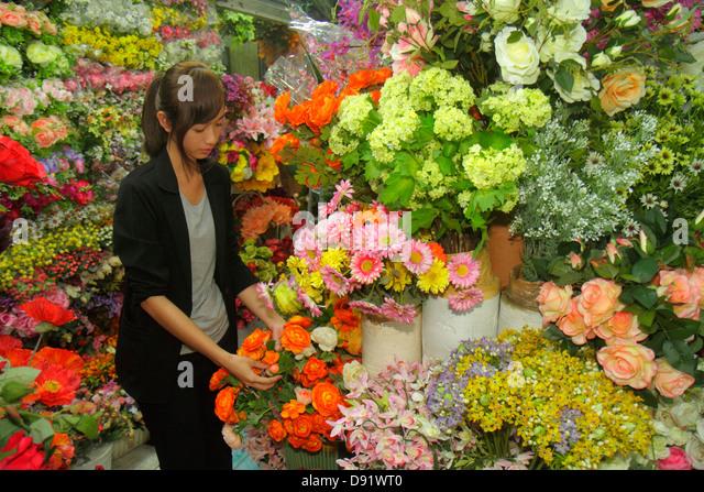Bangkok Thailand Chatuchak Jatujak Weekend Market J.J. marketplace flea shopping Asian woman artificial flowers - Stock Image