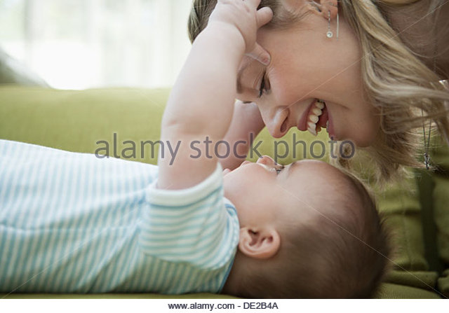 Close up of mother looking down at baby son - Stock Image