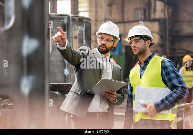Manager and steel worker talking and looking away in factory - Stock Image