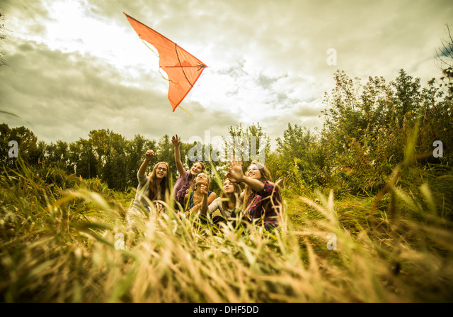 Five young women having fun with kite in scrubland - Stock Image