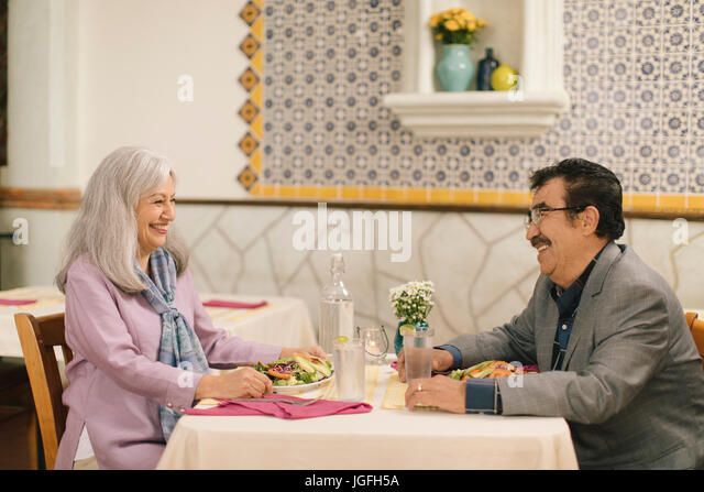 Smiling older couple eating salad and laughing in restaurant - Stock Image