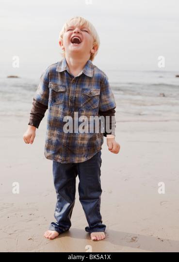 Boy laughing on beach - Stock-Bilder