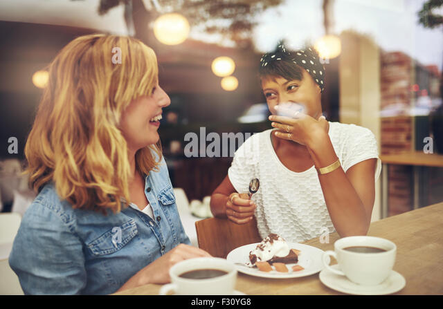 Two good female friends enjoying a cup of coffee together in a coffee house with one laughing as the other makes - Stock Image