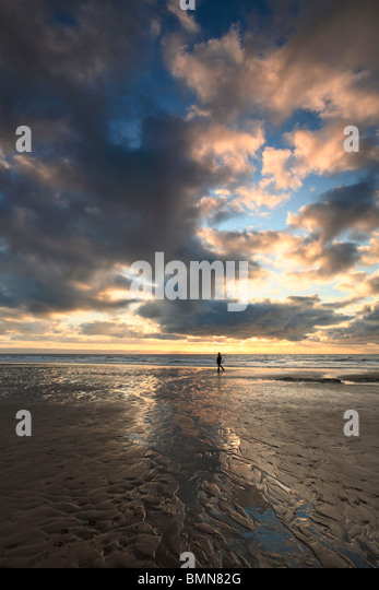 A lone waker silhouetted beneath a dramatic winter sky over Dunraven Bay in Southern Wales - Stock Image