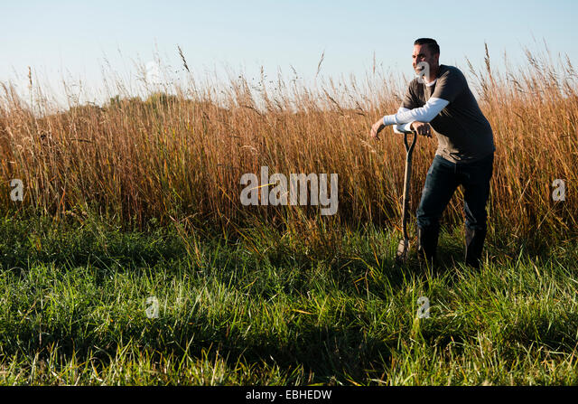 Portrait of mid adult male farmer leaning on spade in field, Plattsburg, Missouri, USA - Stock Image