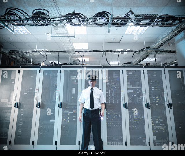 Security guard standing in server room - Stock Image