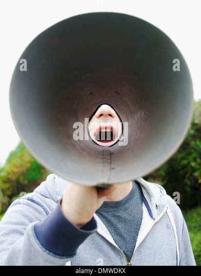 A man using a megaphone in  open air. - Stock Image