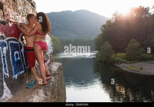 Young couple sharing a kiss on rock ledge, Hamburg, Pennsylvania, USA - Stock-Bilder