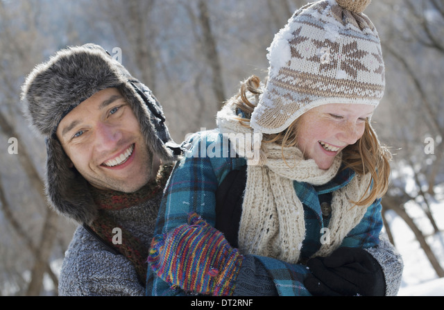 Winter scenery with snow on the ground A young girl with a bobble hat and scarf and a man hugging her - Stock Image