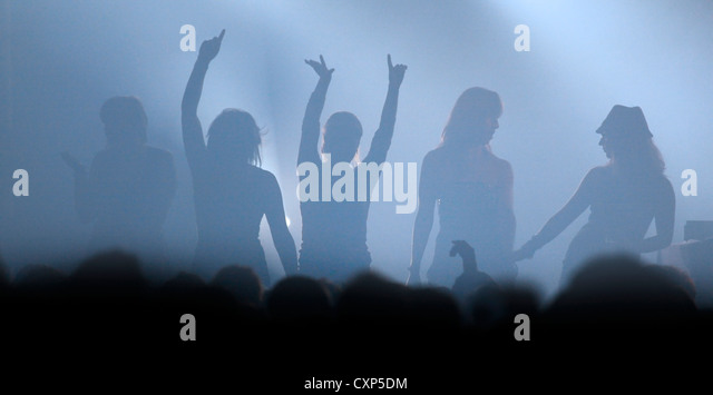 Ambiance during live rock concert with silhouetted female rockers dancing on stage with arms up in the air - Stock Image