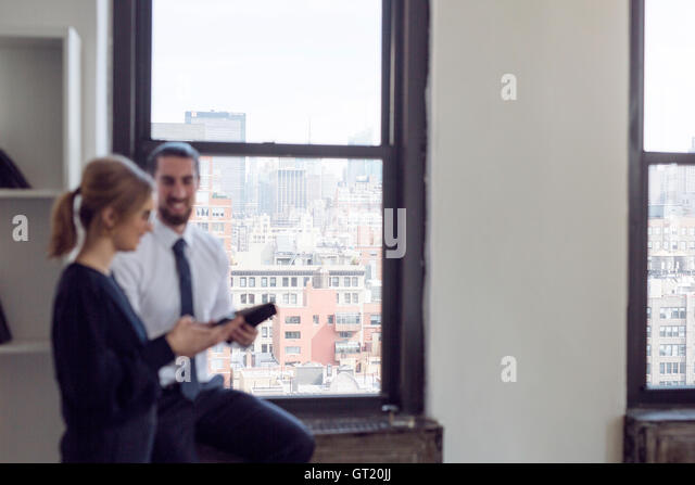 Smiling businessman with female colleague standing by window - Stock-Bilder