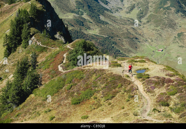 Austria, Kleinwalsertal, Mid adult man running on mountain trail - Stock Image