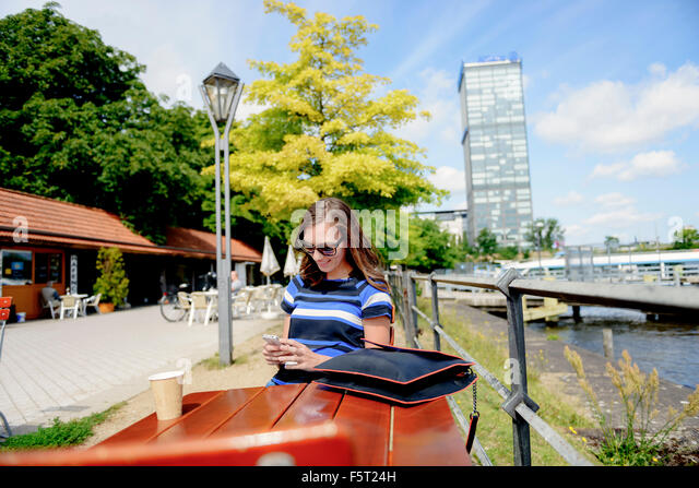 Germany, Berlin, Treptower Park, Woman using phone at cafe table - Stock Image