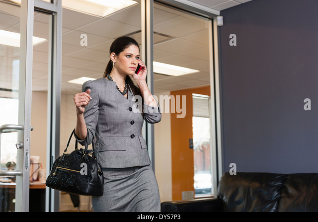 Young businesswoman leaving office, on phonecall - Stock-Bilder