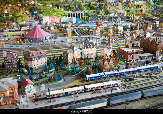 Electric model railroad display with various passenger trains, buildings and other scenery - Stock Image