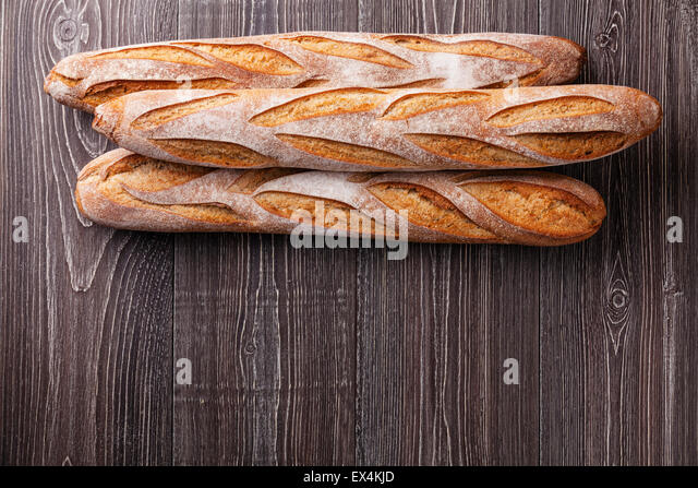 Three fresh French Baguette on gray wooden background - Stock Image