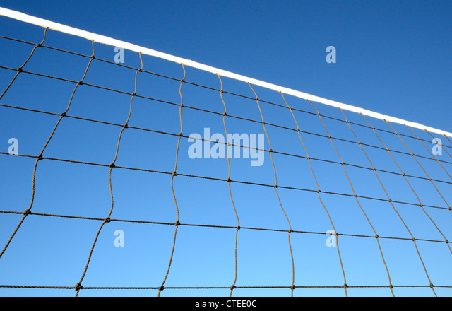 Part of volleyball net against clear blue sky - Stock Image