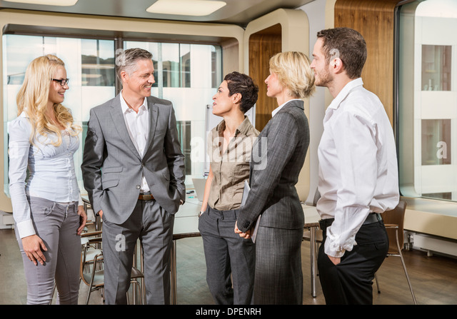 Businesspeople standing in conference room - Stock-Bilder