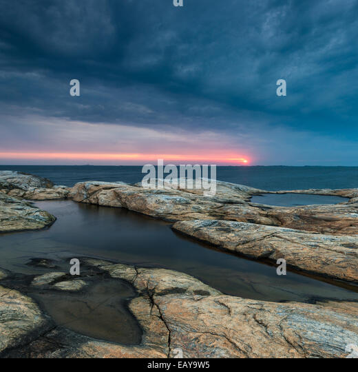Rocky coast with dramatic sky during sunset - Stock Image