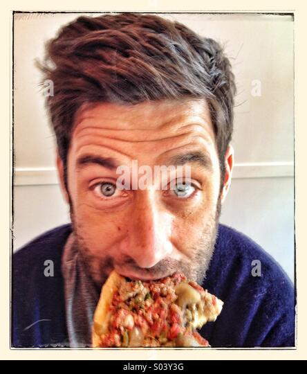 Guy eating pizza - Stock Image