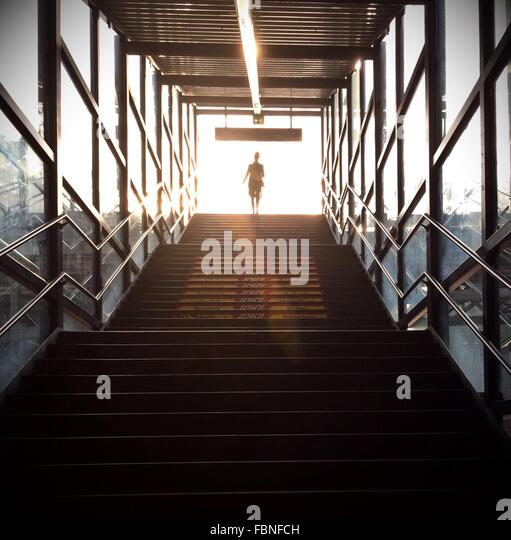 Low Angle View Of Silhouette Woman Walking Up Stairs - Stock Image