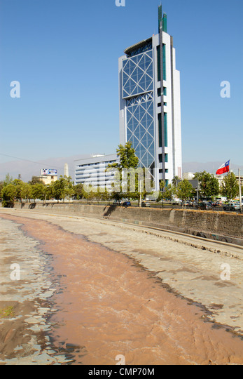 Chile Santiago Rio Mapocho river bank contaminated water stream bed geography building skyscraper Telefonica Chile - Stock Image