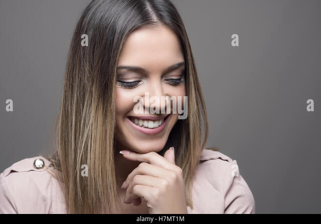Shy pretty woman smiling with closed eyes over gray studio background - Stock Image