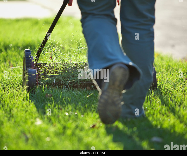 Woman cutting grass with environmentally friendly lawn mower. Winnipeg, Manitoba, Canada. - Stock-Bilder