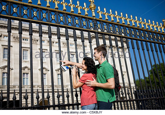 A young couple taking a picture of Buckingham Palace - Stock Image