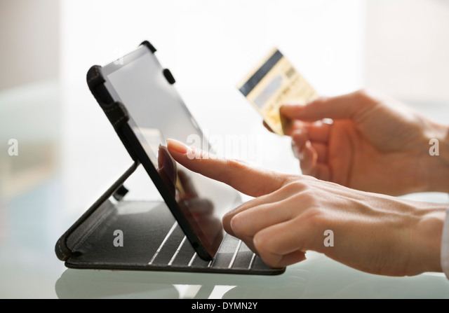 Woman shopping using tablet computer and credit card - Stock Image