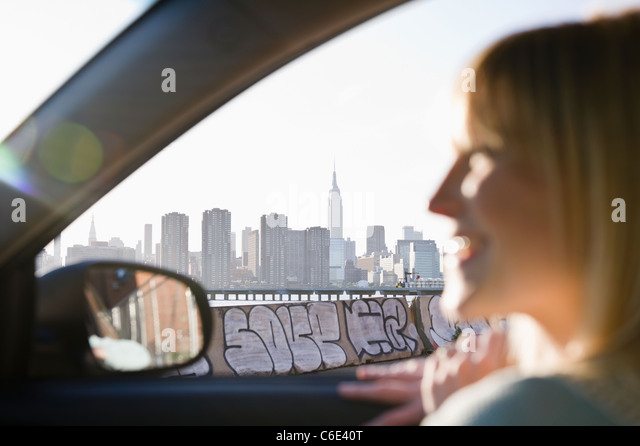 USA, Brooklyn, Williamsburg, Woman driving through city - Stock Image