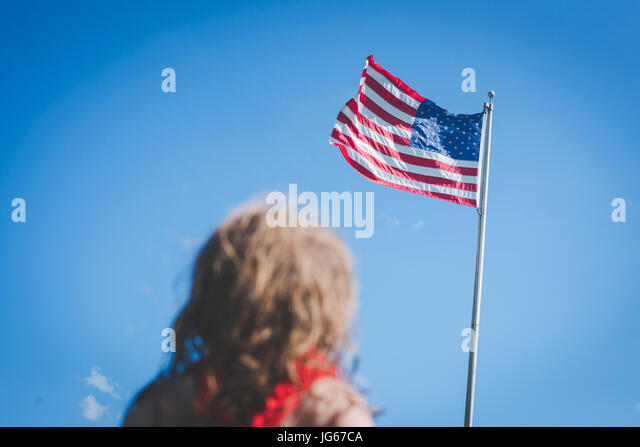 A young girl looks up at American flag. - Stock Image