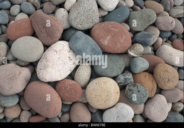 Multi-coloured stones on a beach - Stock Image