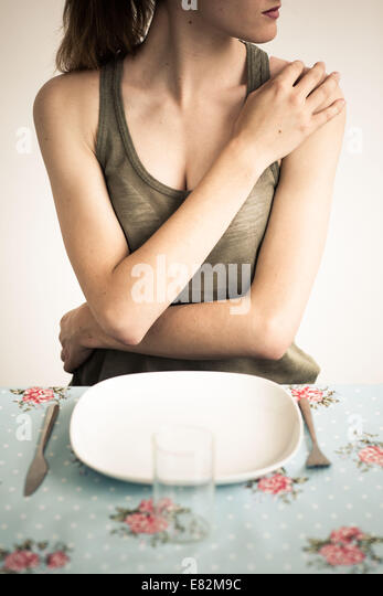 Woman in front of an empty plate. - Stock-Bilder