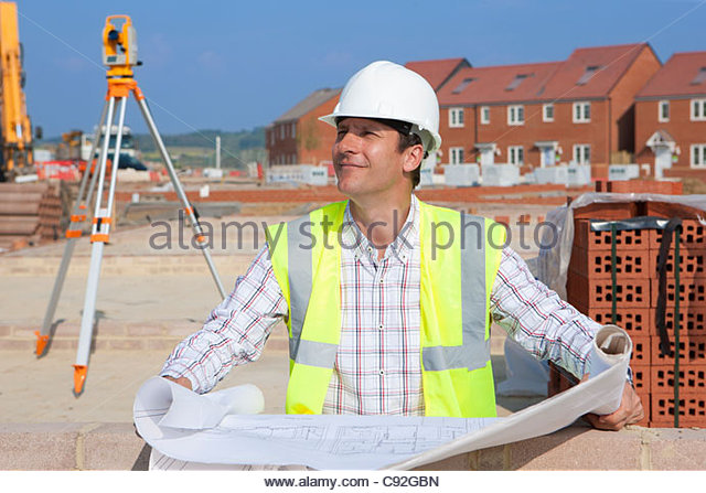 Architect with blueprints at construction site - Stock-Bilder