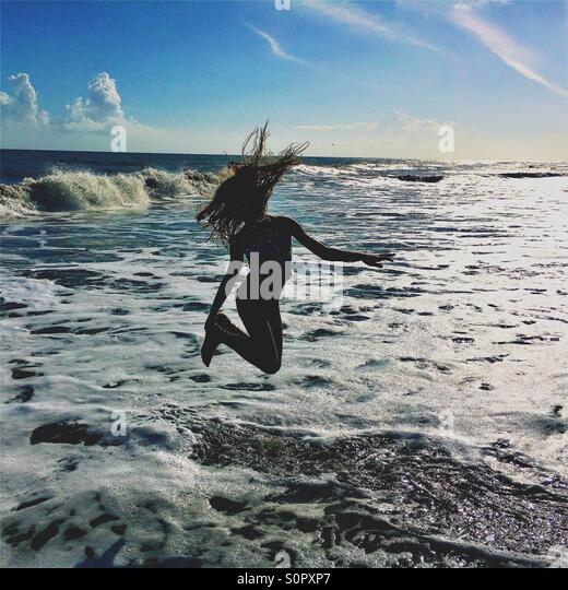 Girl jumping in the ocean waves - Stock Image