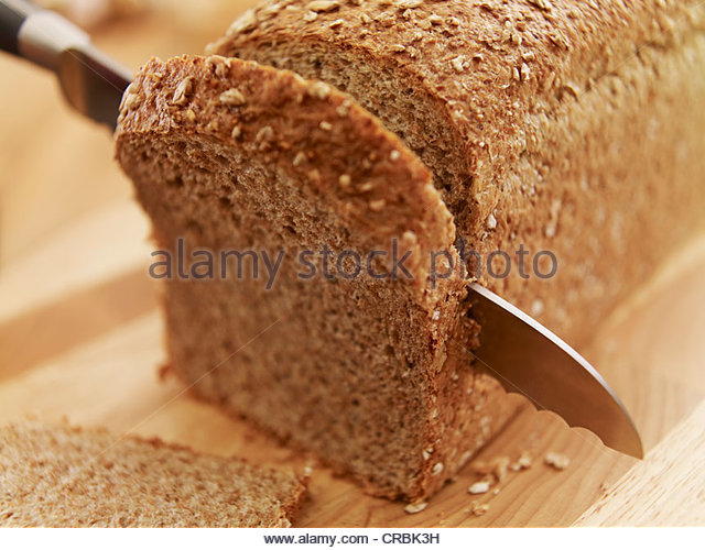 Knife slicing fresh bread loaf - Stock Image