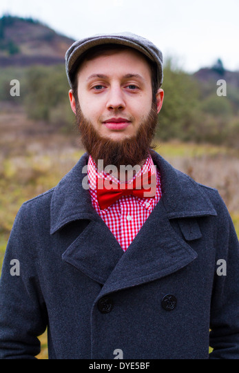 Trendy hipster guy outdoors in the winter in a fashion portrait of the handsome man. - Stock-Bilder