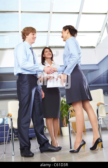 Businesswoman shaking hands with businessman after making final decision - Stock Image