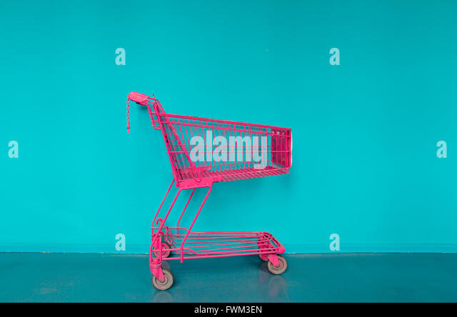 Shopping Cart Against Blue Wall - Stock Image