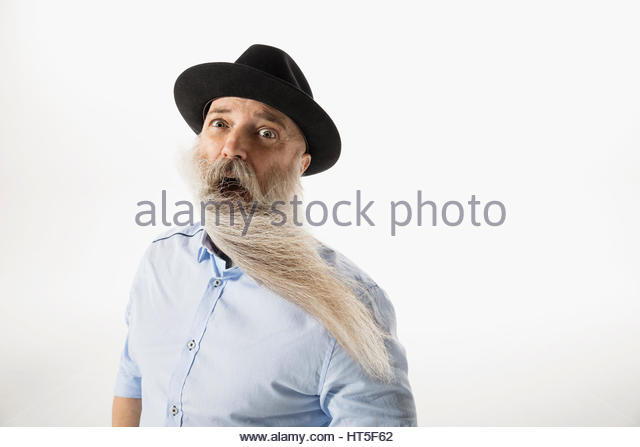 Portrait surprised hipster with wind blowing beard against white background - Stock-Bilder
