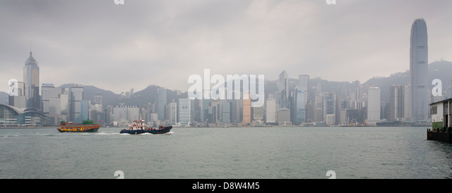 Panorama of Hong Kong Island on a misty day seen across the harbour from Tsim Sha Tsui, Kowloon - Stock Image